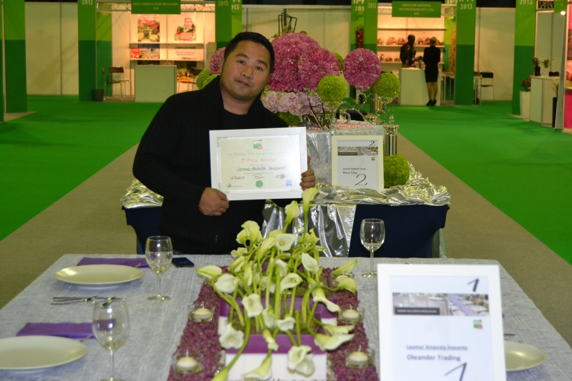 Leomar A. Inocente, Head Florist of Oleander Trading Dubai, holds his certificate as 2nd prize of Wedding Table Championship #